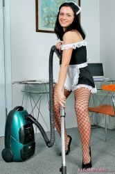 Horny brunette maid Cortney in fishnet pantyhose posing with vacuum cleaner