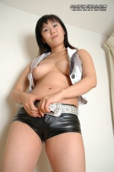 Asian brunette girl in black leather shorts stretches pink vagina